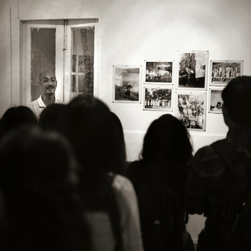 Tawatchai Pattanaporn presenting his work at the final night exhibition in Rangoon. ©Philip Blenkinsop / VII