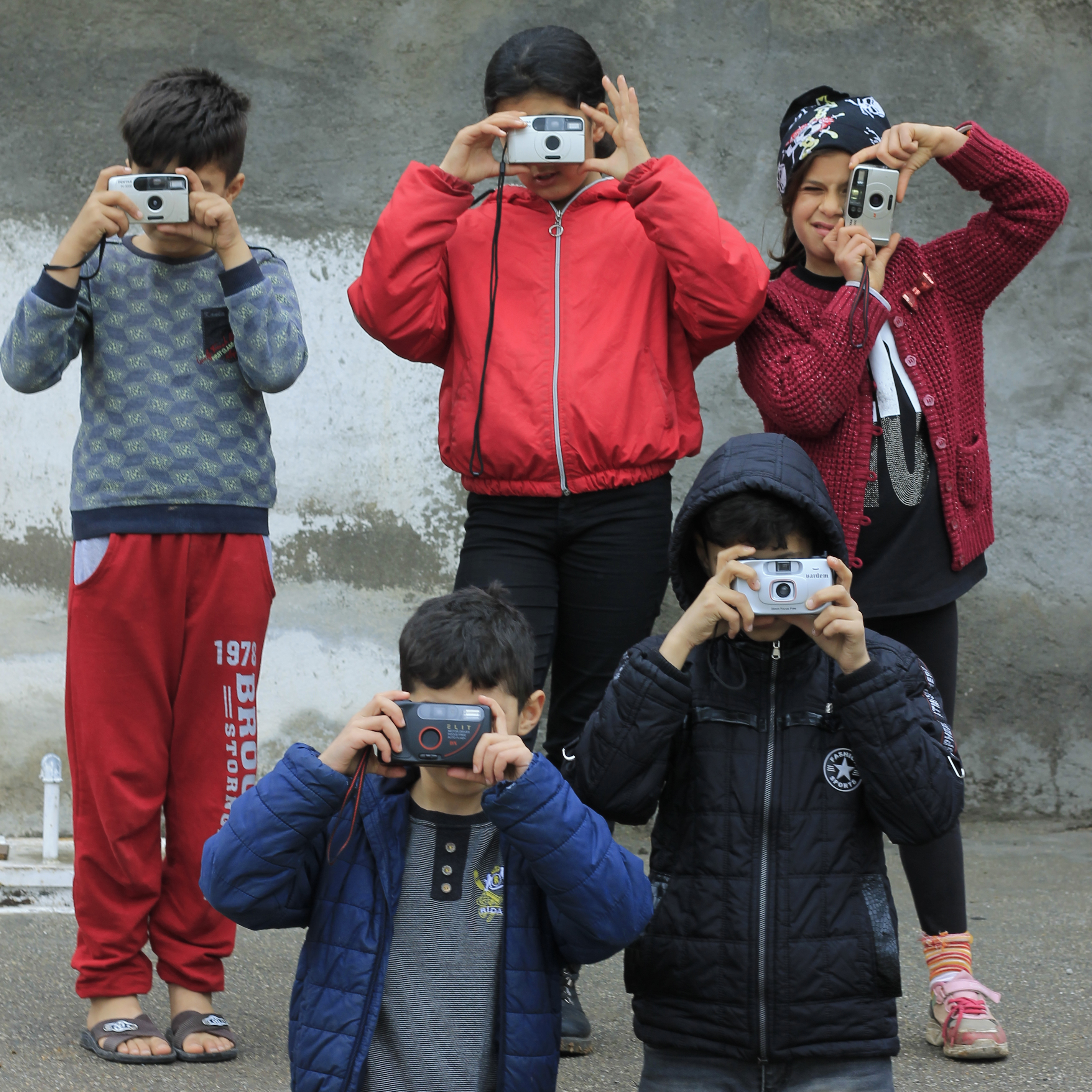 Participants of Sirkhane Darkroom posing with cameras during the workshop. ©Serbest Salih